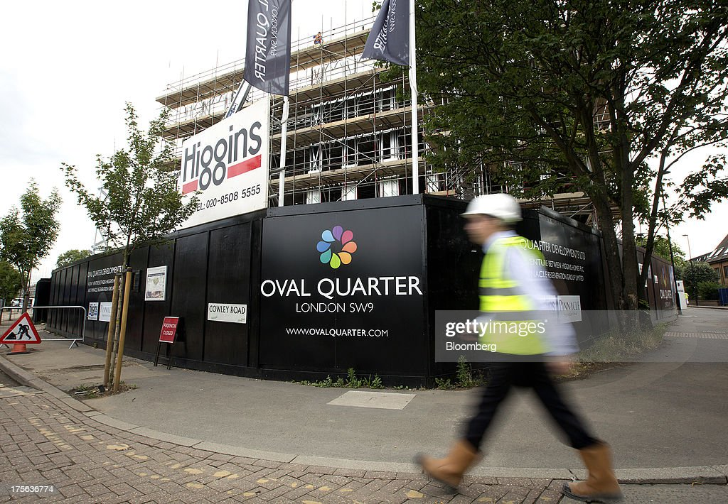 A construction worker passes hoardings outside the Oval Quarter, a shared ownership, private and social residential housing complex developed by Higgins Group Plc in partnership with Nottinghill Housing and Pinnacle Regeneration Group, in London, U.K., on Monday, Aug. 5, 2013. U.K. house prices rose 0.8 percent in July, from 0.3 percent the previous month, Nationwide Building Society said. Photographer: Simon Dawson/Bloomberg via Getty Images