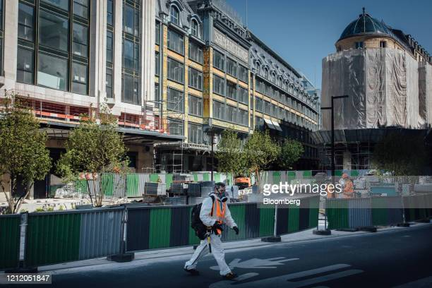 A construction worker passes the Samaritaine luxury department store operated by LVMH Moet Hennessy Louis Vuitton during renovation work in Paris...