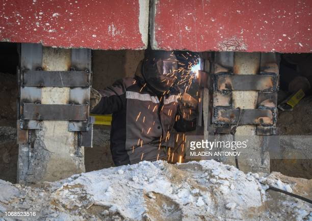 A construction worker performs emergency welding works on the structure of a cracked panel building in the eastern Siberian city of Yakutsk on...