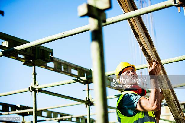 Construction worker placing plank