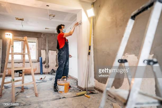 bouwvakker die concrete muur bepleistert en gladstrijkt - beëindigen stockfoto's en -beelden