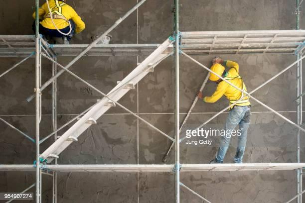 construction worker plastering cement on concrete block wall - estructura de edificio fotografías e imágenes de stock