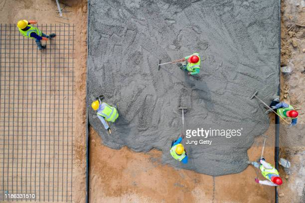 a construction worker pouring a wet concret at road construction site - cement stock pictures, royalty-free photos & images