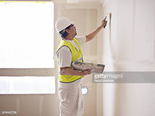 Construction worker prepares drywall