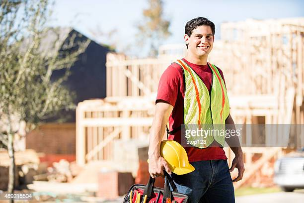 Construction worker prepares for work at job site. Building. Tools.