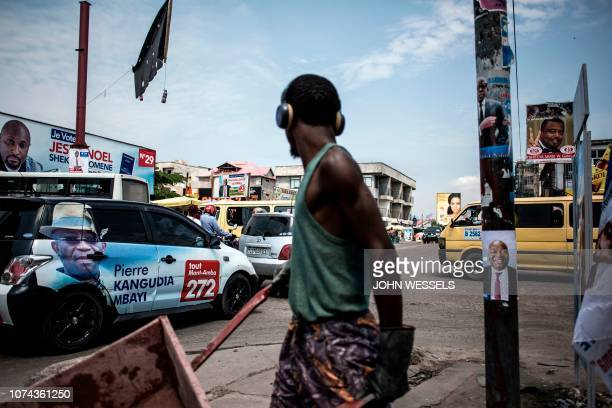 TOPSHOT A construction worker pushes a wheelbarrow past a campaign car and posters at a busy intersection in the district of Lingwala in Kinshasa on...