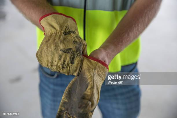 construction worker putting on protective gloves - work glove stock photos and pictures