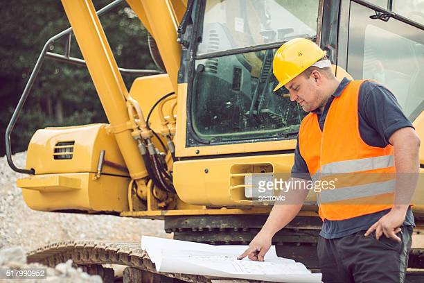 Construction worker reading blueprints