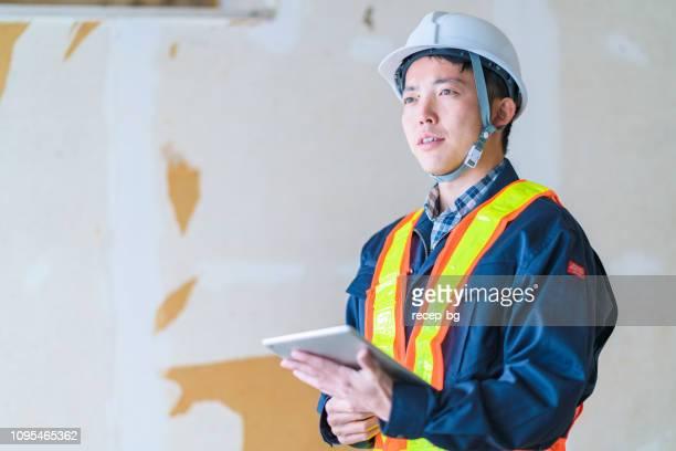 建設労働者読書デジタル タブレット - 建設現場 ストックフォトと画像