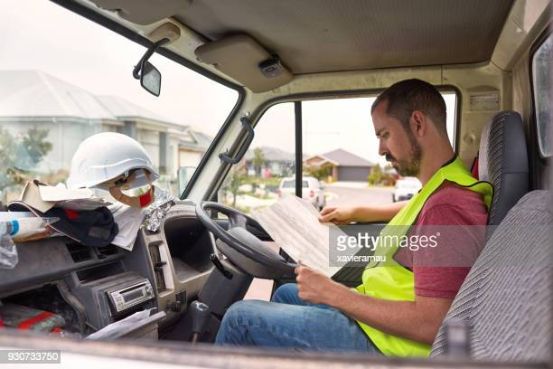 Construction worker reading paper in pick-up truck