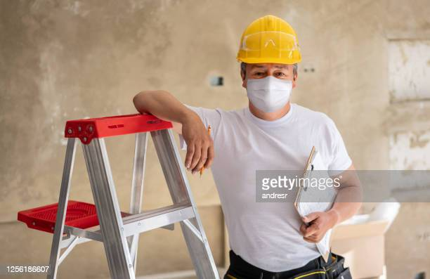 construction worker remodeling a house and wearing a facemask - biosecurity stock pictures, royalty-free photos & images