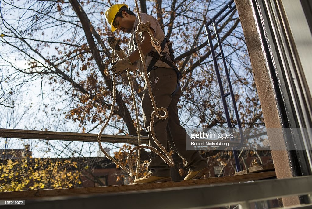 A construction worker removes scaffolding November 22, 2012 from the exterior of a brownstone building in the Brooklyn borough of New York.