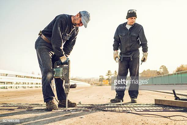 Construction worker repairing bridge with a drill.