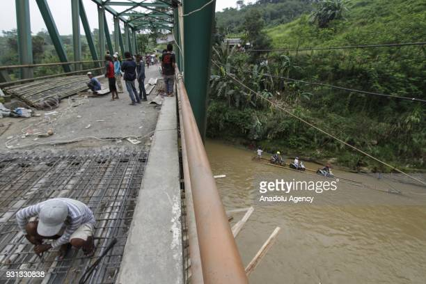 A construction worker repairs the bridge while under the bridge several people assist motorcyclists to pull up their vehicles onto wooden raft to...