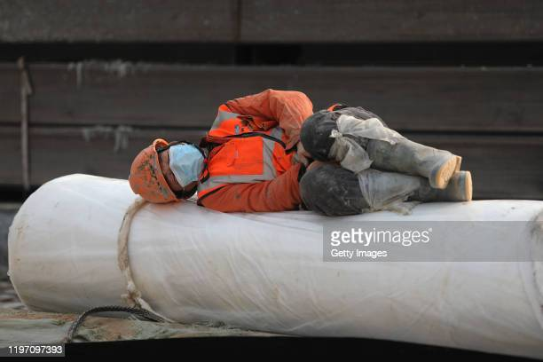 A construction worker rests as new hospitals are built to tackle the coronavirus on January 28 2020 in Wuhan China Wuhan Huoshenshan hospital will...
