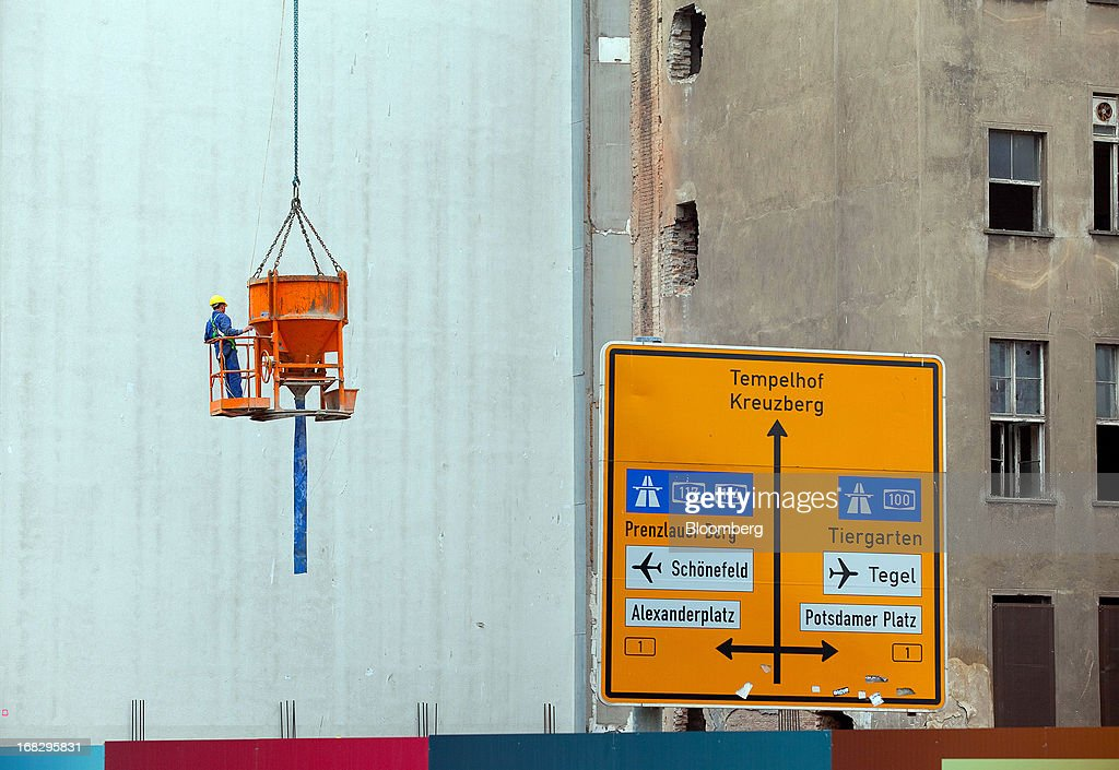 A construction worker rides a crane bucket, used for delivering cement on the building site for the Leipziger Platz shopping mall, Berlin's largest commercial project by developer High Gain House Investments GmbH (HGHI) in Berlin, Germany, on Wednesday, May 8, 2013. Germany, Europe's largest economy, reported growth in the construction industry during April, according to Markit Economics. Photographer: Krisztian Bocsi/Bloomberg via Getty Images