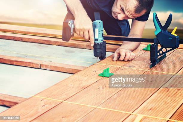 Construction worker screwing down wood deck with battery power screw gun or drill.