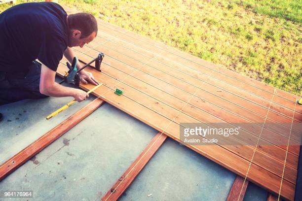 construction worker screwing down wood deck with battery power screw gun or drill. - deck stock pictures, royalty-free photos & images