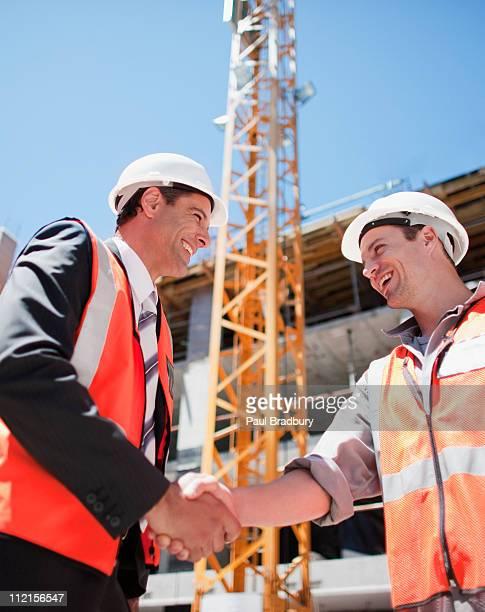 Bauarbeiter die Hand schütteln, auf Baustelle
