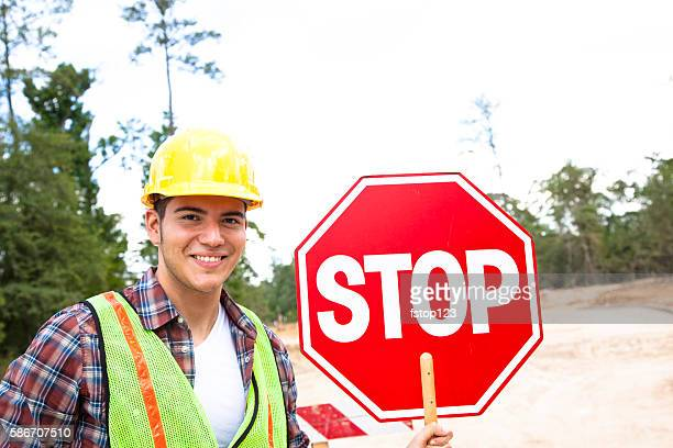 Construction worker, signalman holds stop sign at job site.