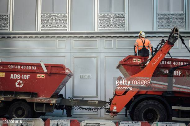 A construction worker signas during a skip delivery outside the Christian Dior SE luxury goods store operated by LVMH Moet Hennessy Louis Vuitton SE...