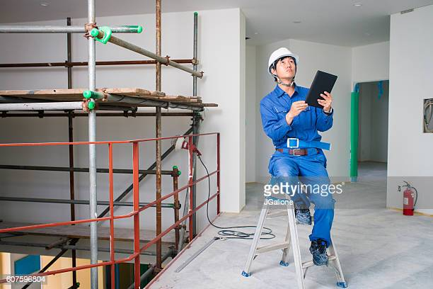 Construction worker sitting on a ladder whilst inspecting a site