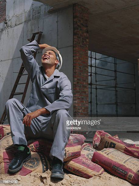 Construction worker sitting on cement sack, looking up, laughing