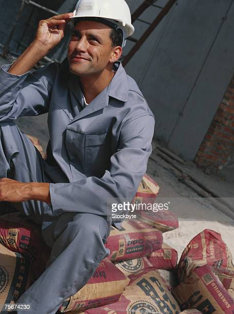 Construction worker sitting on cement sack, smiling
