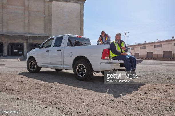 construction worker sitting on their pick-up truck having lunch break - lunch break stock photos and pictures