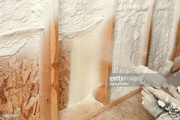 Bauarbeiter sprühen dehnbare Schaumstoff-Isolierung zwischen der Stollen