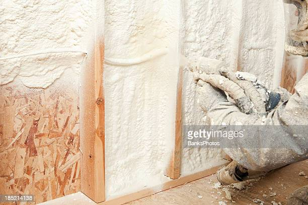 Construction Worker Spraying Expandable Foam Insulation between Wall Studs