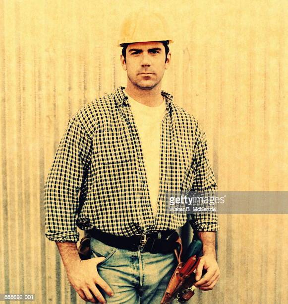Construction worker standing against wall (transfer image)