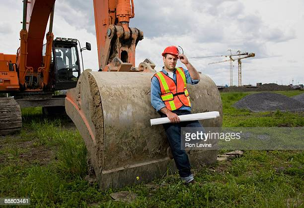 Construction worker standing by bulldozer