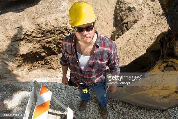 Construction worker standing by hole in road, elevated view, portrait