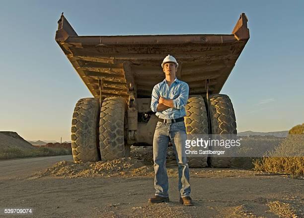 Construction Worker Standing near Dump Truck
