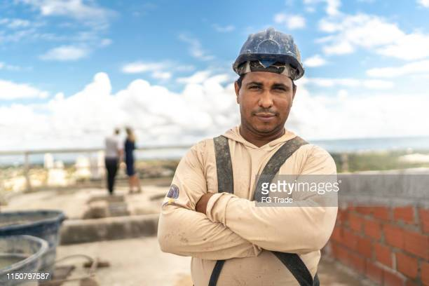 construction worker standing with arms crossed in a construction site - building contractor stock pictures, royalty-free photos & images
