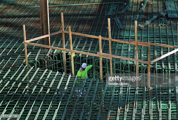 A construction worker stands below steel reinforcement bars at Pier 4 in Boston where a ninestory 106unit residential building designed by...