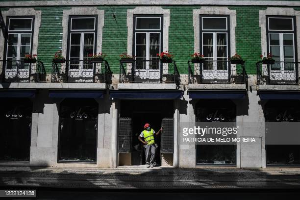 Construction worker stands in front of a building in downtown Lisbon on June 23, 2020. - Portugal's Prime Minister Antonio Costa said on June 22,...