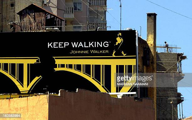 A construction worker stands on a rooftop of a building behind a Johnnie Walker whiskey advertisement with a twist on their classic advertising...