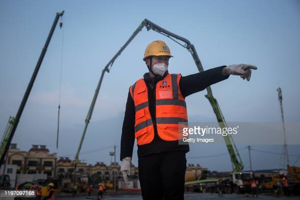 A construction worker supervises as new hospitals are built to tackle the coronavirus on January 28 2020 in Wuhan China Wuhan Huoshenshan hospital...