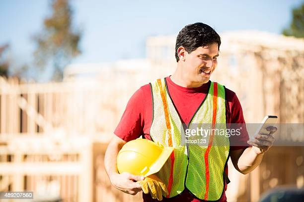 Construction worker, supervisor checks cell phone. Working at building site.