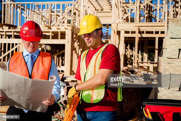 Construction worker, supervisor discuss blueprints at work site. Building.