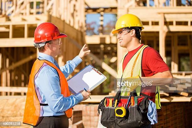 Construction worker, supervisor discuss job at work site. Building.