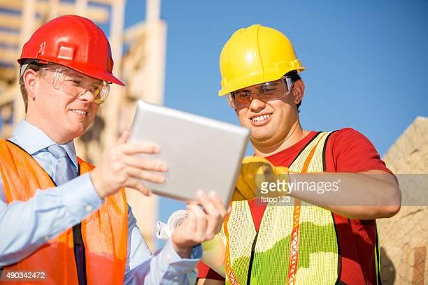 Ouvrier du bâtiment, superviseur, discuter des plans sur tablette numérique.