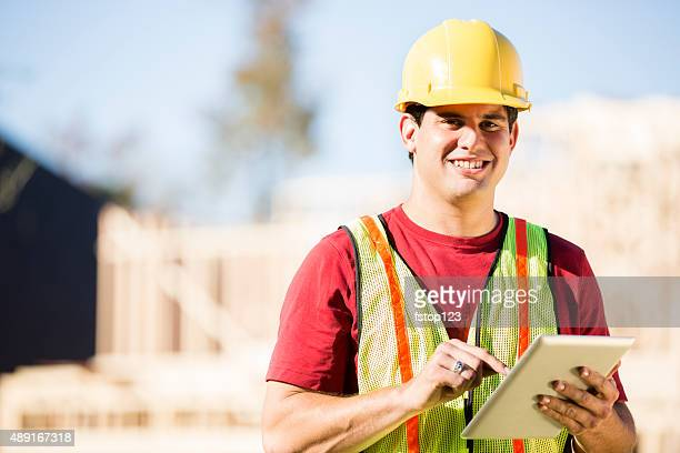 Construction worker, supervisor inspects work at building site. Digital tablet.