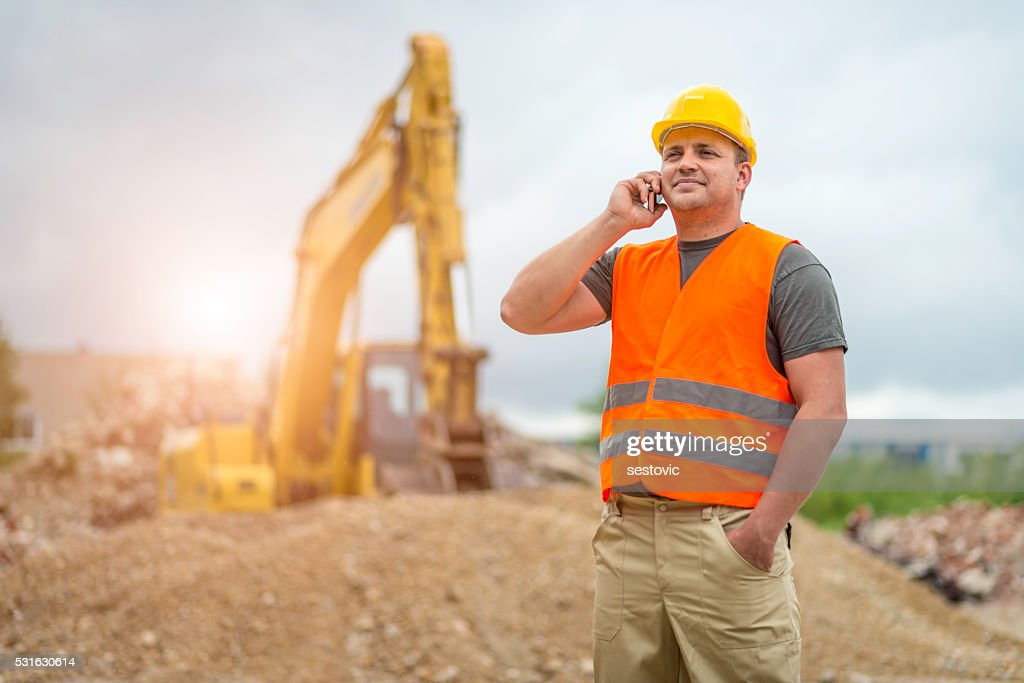 Construction worker takes a call : Stock Photo