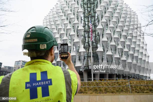 A construction worker takes a photo of the American flag as it hangs at the new US embassy after being raised for the first time on January 12 2018...