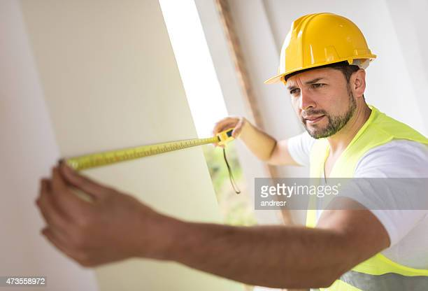 Construction worker taking measurements
