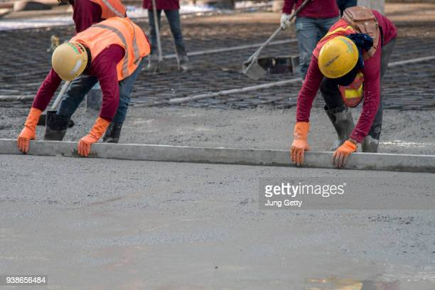 construction worker troweling wet concrete on a top of concrete floor slab new construction site - concrete stock pictures, royalty-free photos & images