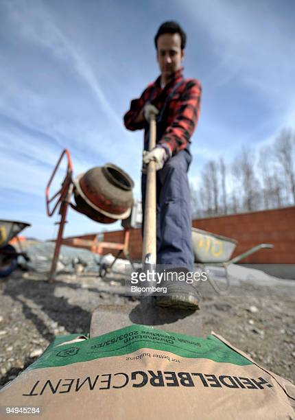 A construction worker uses a shovel to open a sack of HeidelbergCement on a construction site near Rosenheim Germany on Friday March 13 2009...